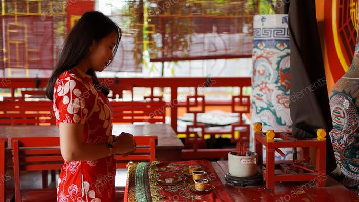 asian girl praying and wishing a happy chinese new year at vihara