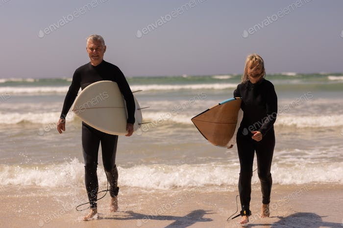 Front view of senior couple with surfboard walking on beach in the sunshine