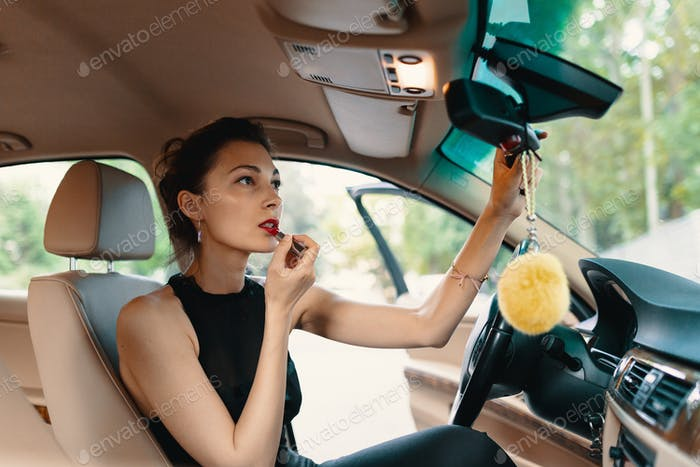 Young elegant woman looking in the car view mirror while applyin