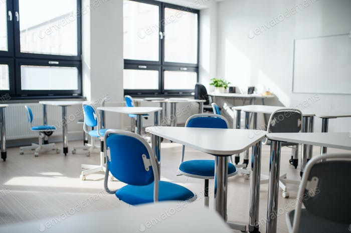 Desks and chairs in empty classroom. Copy space