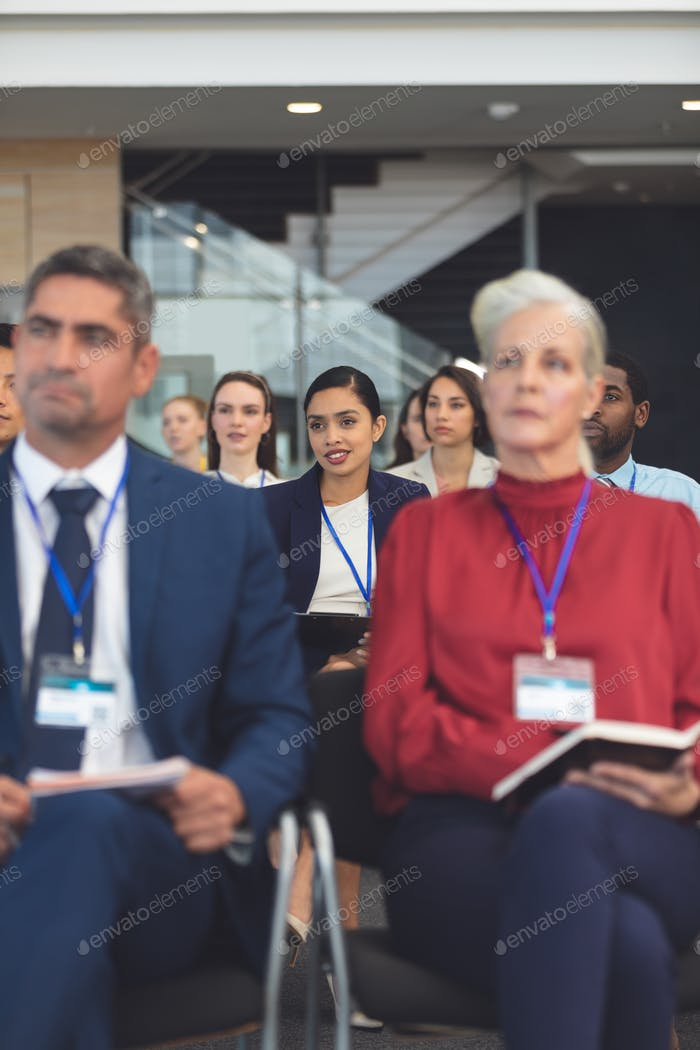 Front view of beautiful young mixed race businesswoman at a business seminar in office building