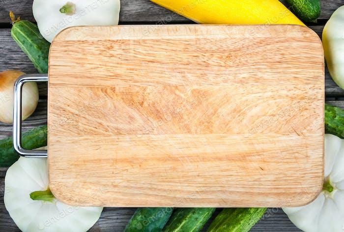 Schneidebrett, frisches Gemüse auf Holztisch. Draufsicht mit