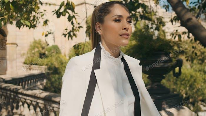 Юная великолепная женщина в белом пиджаке и рубашке уверенно гуляет по старинному красивому парку