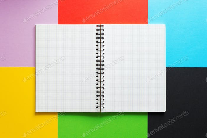 checked notebook at abstract colorful paper