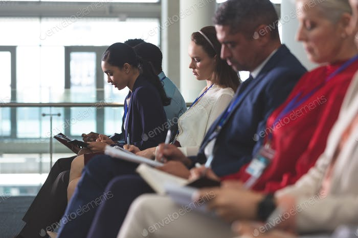 Diverse business people writing on notepads in a business seminar in modern office building