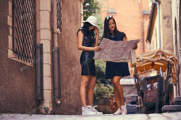 Two women tourists are standing in the middle of a narrow street, and look for sights on the map.
