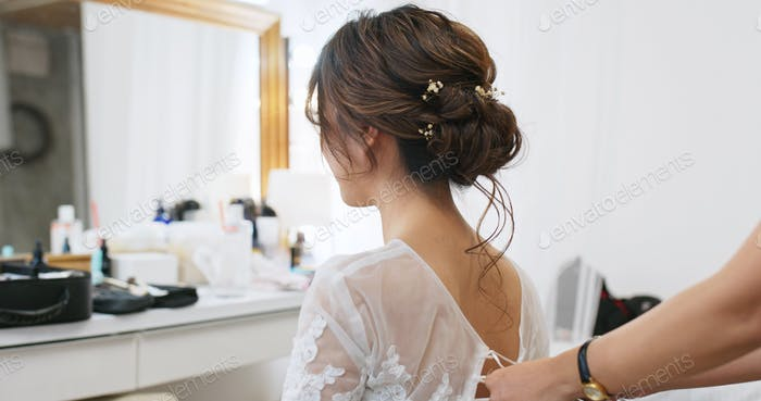 Hairdresser creating a hairstyle for female model in salon