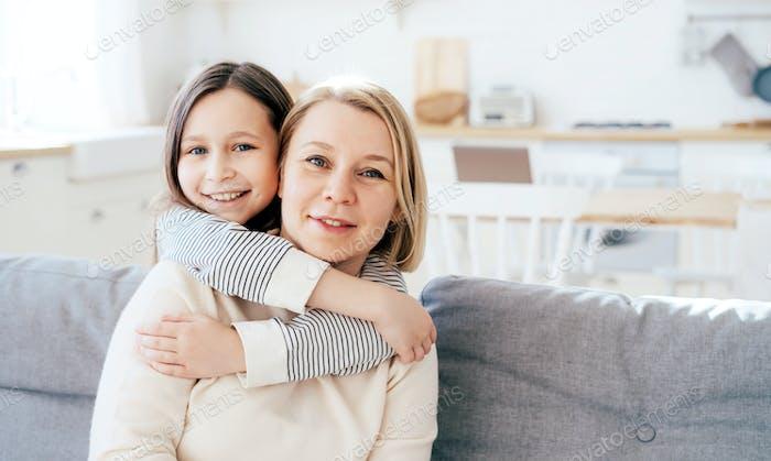 Die Tochter eines Teenagers umarmt sanft und vorsichtig ihre Mutter, die auf der Couch sitzt. Familie Porträt