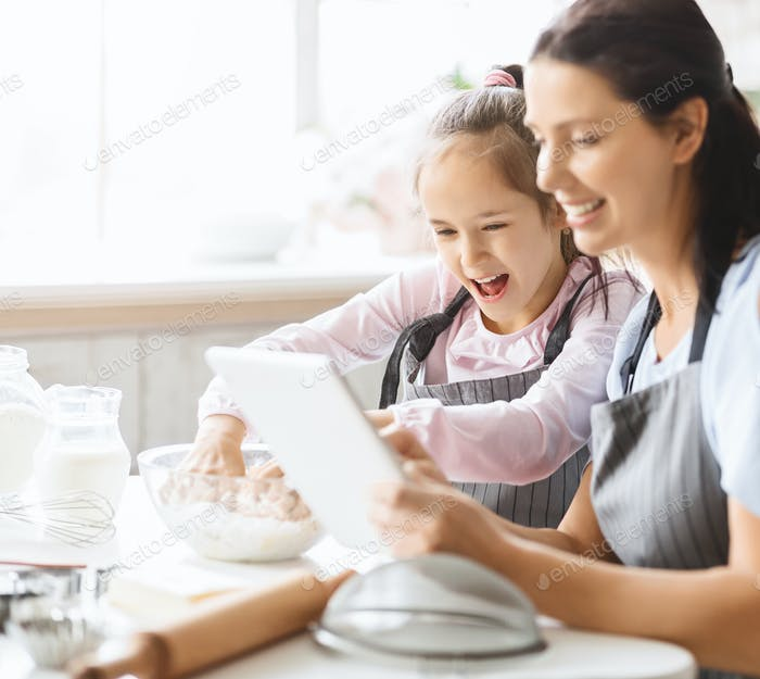 Young woman and daughter watching video recipe on digital tablet