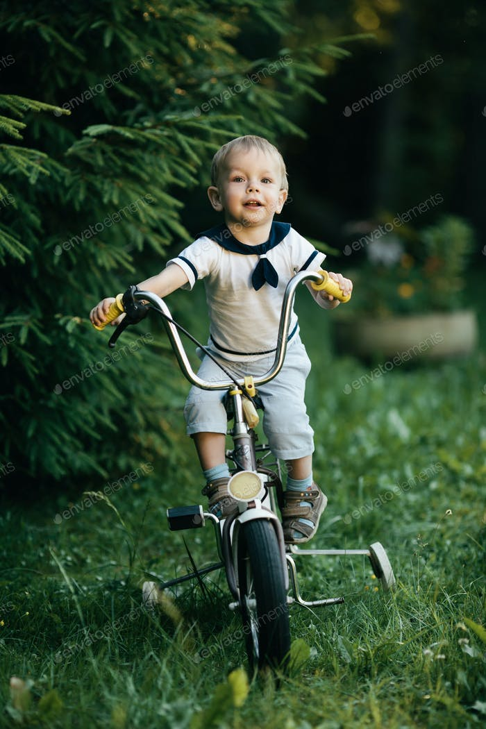 little happy boy on bike