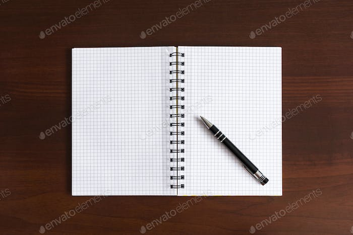 Top view of blank notepad on wooden desk