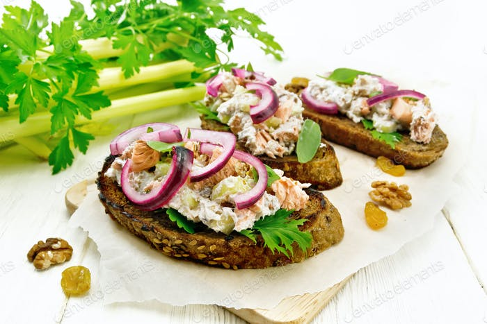 Bruschetta with fish and curd on light wooden board