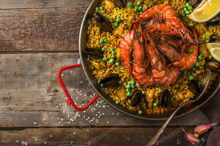 Top view of paella with prawns, mussels and lemon, wooden background, copy space