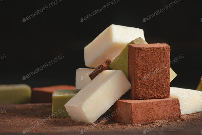 Assortment of soft chocolates on a black background with copy space. Milk and matcha Japanese