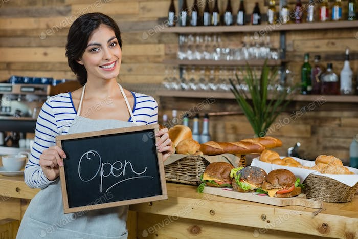 Portrait of waitress holding open signboard at counter