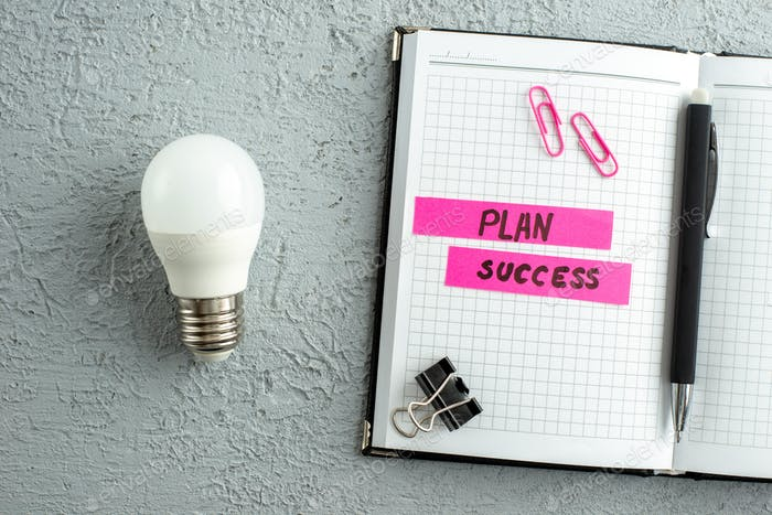Top view of plan succeess writings pen and open spiral notebook light bulb on gray sand background