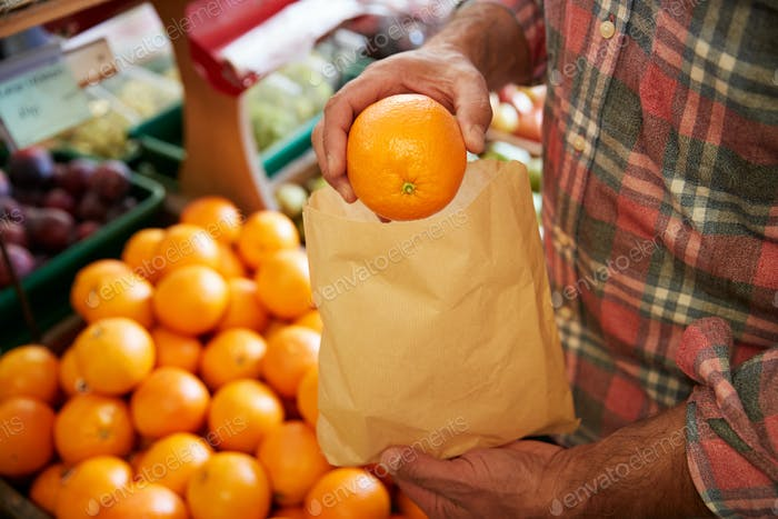 Close Up Of Male Customer With Paper Bag Buying Fresh Oranges In Organic Farm Shop