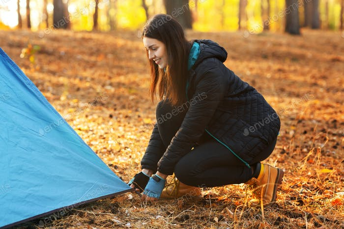 Happy adventurous girl setting camp in autumn forest