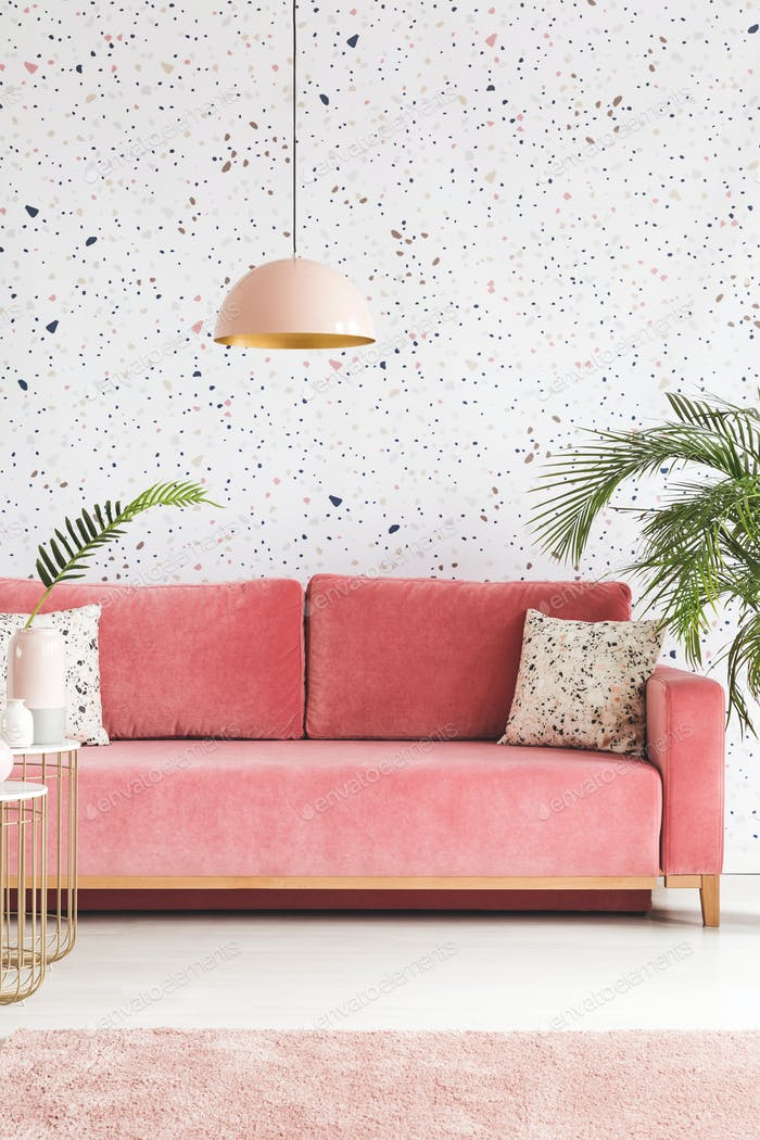 Real photo of a pink sofa with pillows, chandelier and patterned