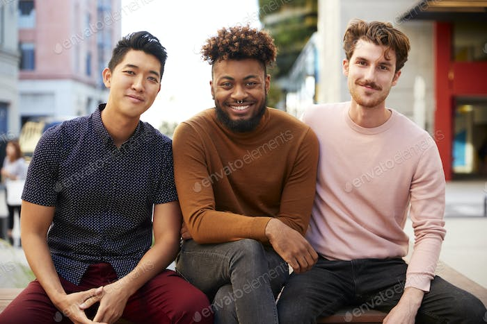 Three millennial male hipster friends on a bench in a city street smiling to camera, close up