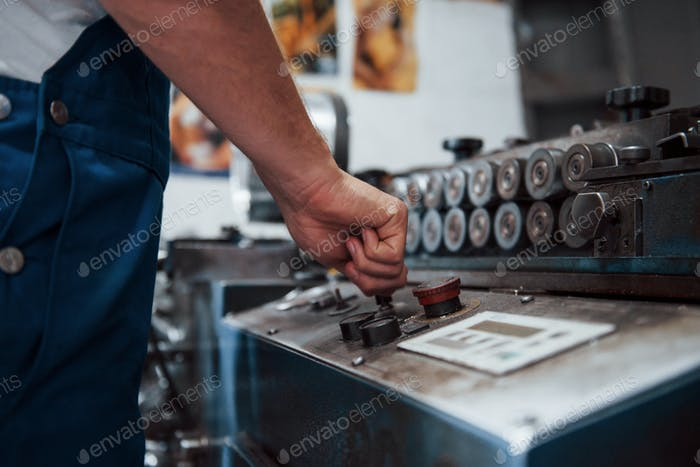 Turns on the machine. Man in uniform works on the production. Industrial modern technology