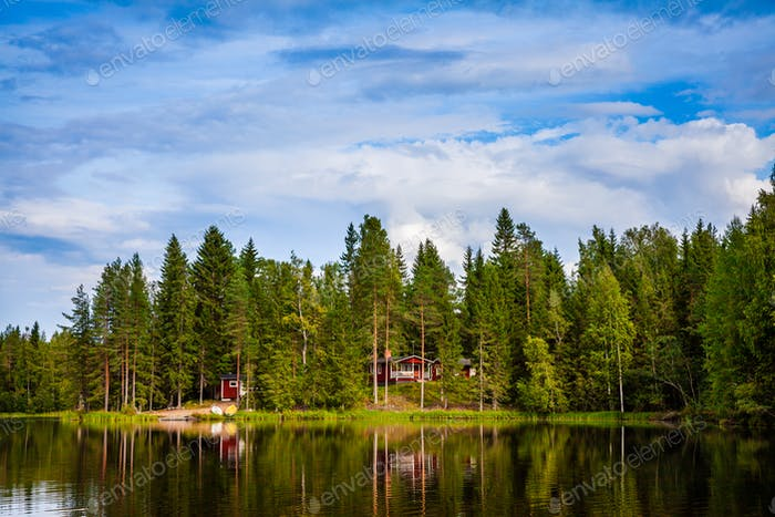 Red wooden cottage by the lake