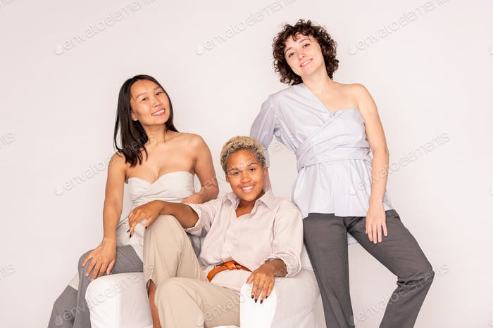 Happy young African woman in casualwear sitting between intercultural friends