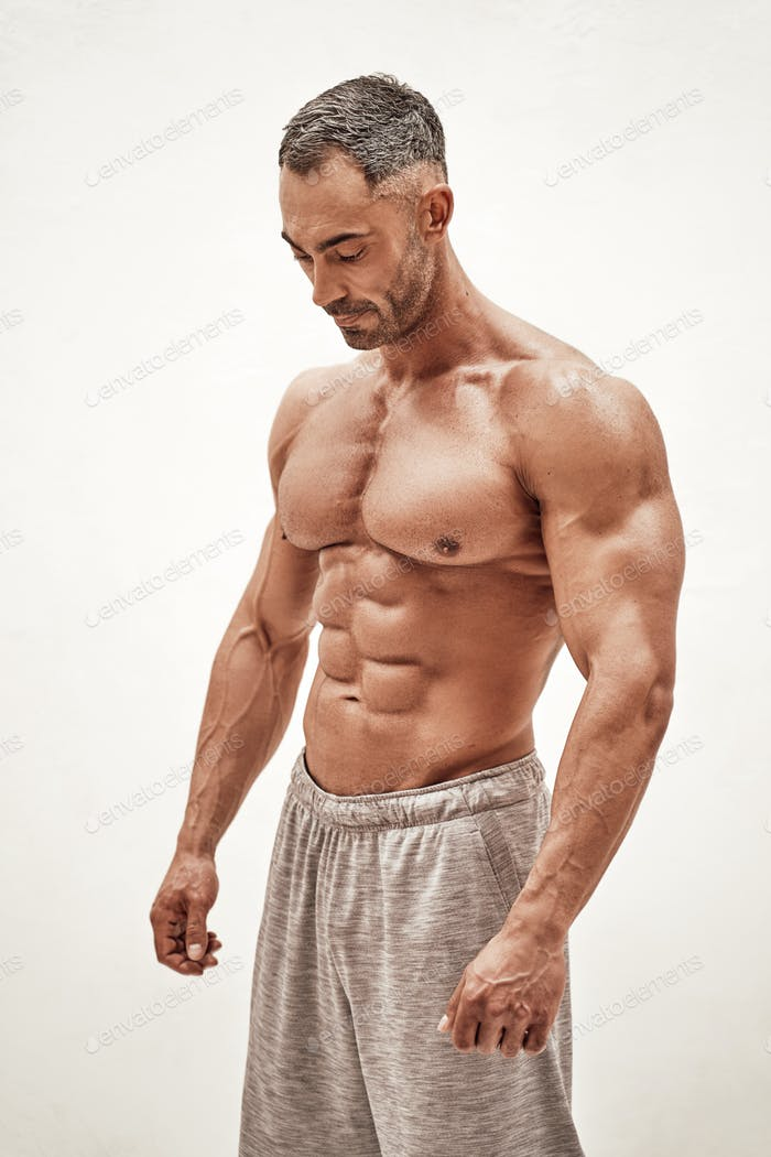 Strong and powerful man bodybuilder looking down in a bright studio