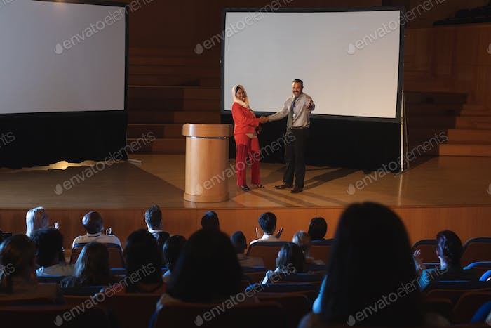 Business colleague discussing with each other in front of the audience while shaking hand