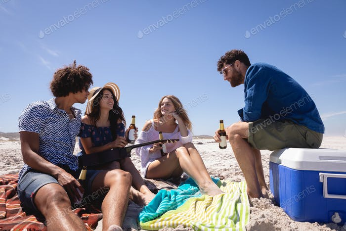 Happy group of friends having fun at beach in the sunshine while they are drinking beers
