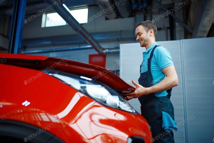 Worker in uniform opens vehicle hood, car service