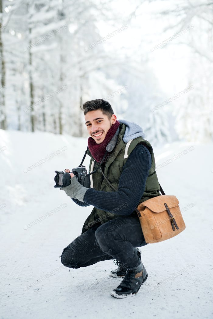 Young man with camera outdoors in snow in winter forest, looking at camera.