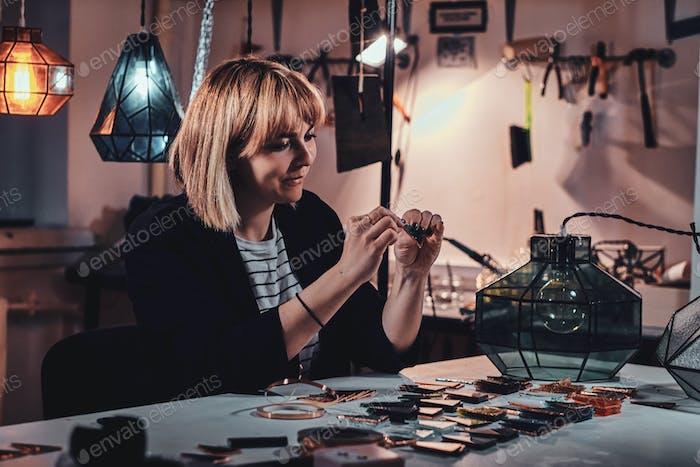 Женщина работает над своим проектом лампы в студии ламп.
