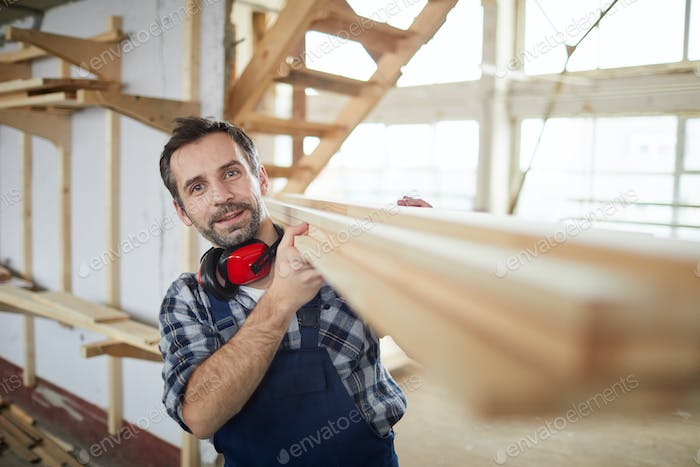 Mature Builder carrying Wooden Boards