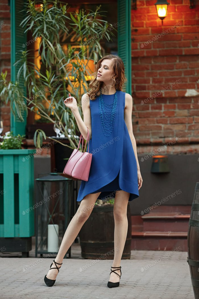 Slim beautiful girl dressed in a blue summer dress holding a pink bag is standing in a city street