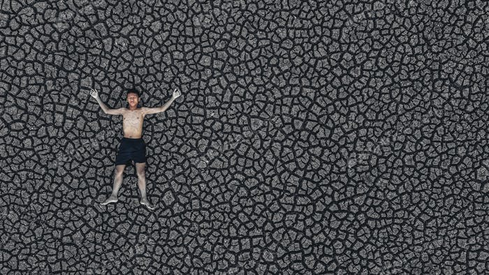 Boys sleep on dry land with dry and cracked soil, global warming