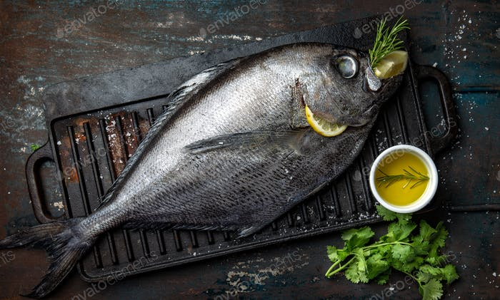 Roher Dorado-Fisch mit Gewürzen Kochen auf Grillbrett Draufsicht.