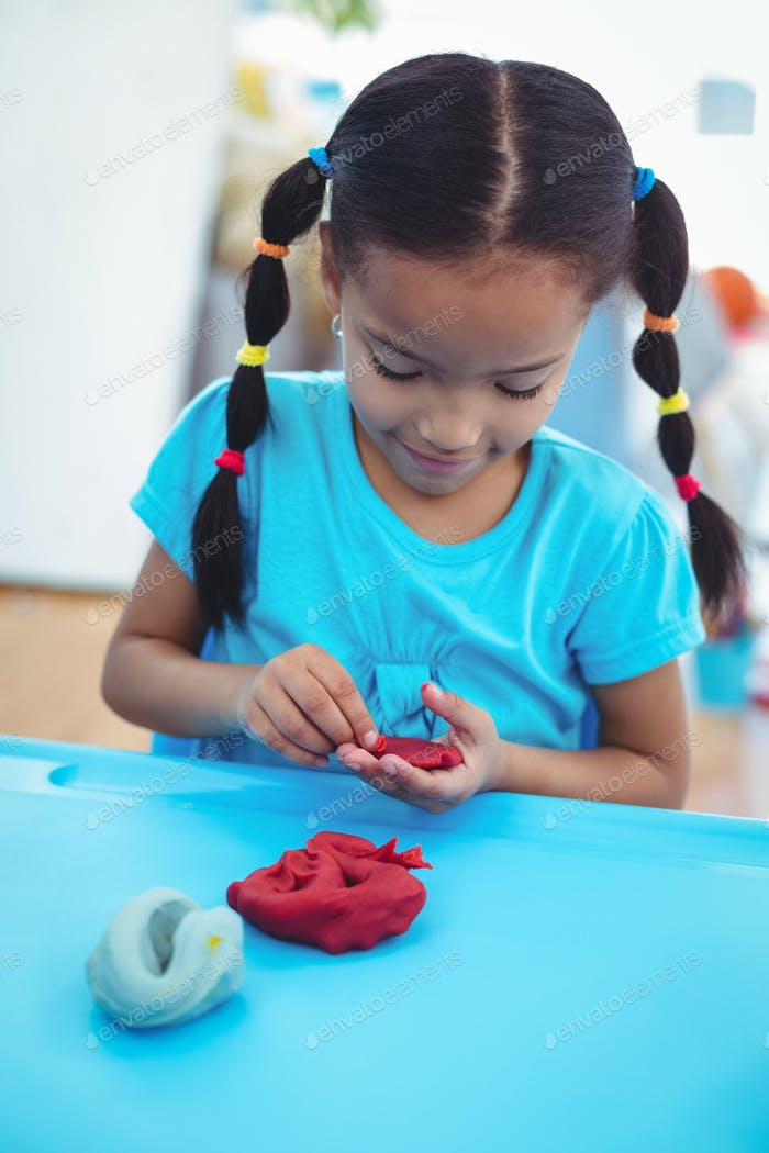 Smiling girl using modelling clay at their desk
