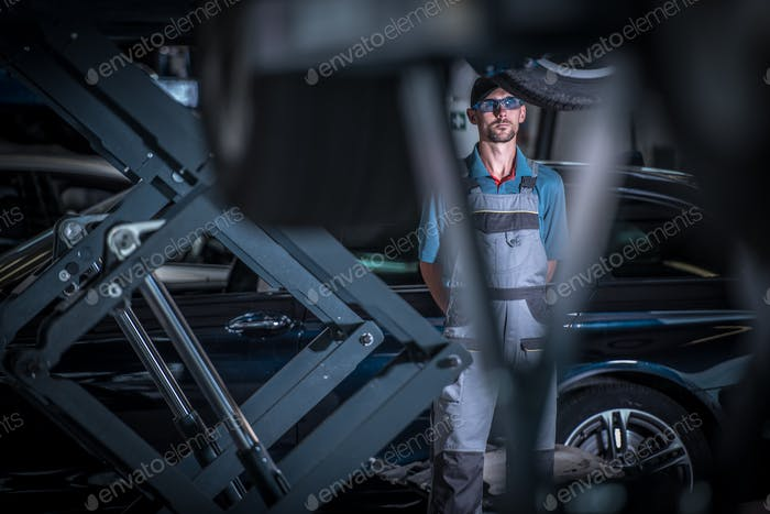 Car Mechanic Between Lifts