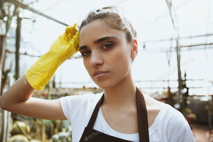 Pretty young woman in glasses standing in greenhouse