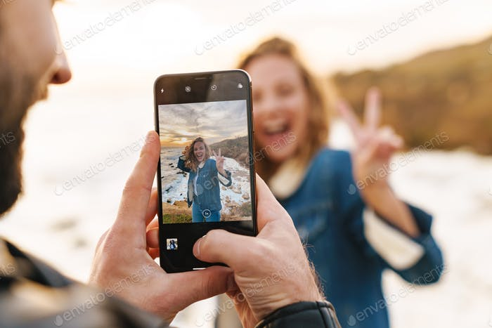 Image of young caucasian couple taking photo on cellphone by seaside