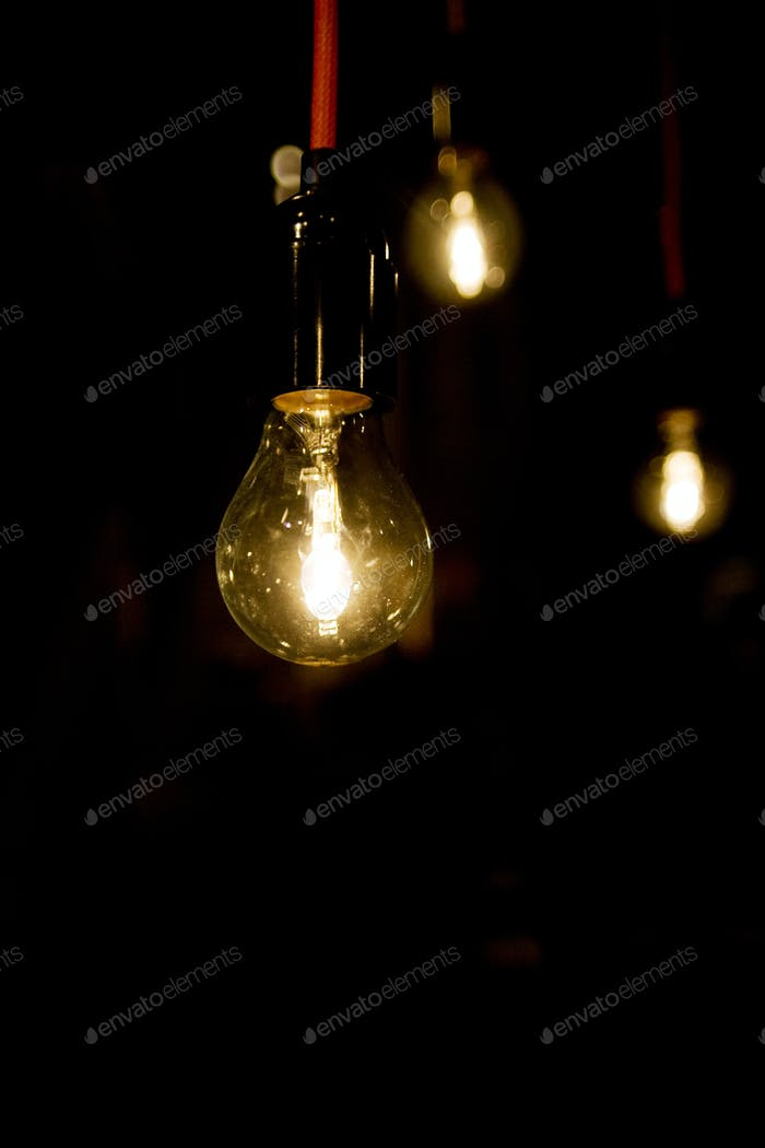 Illuminated light bulbs against black background