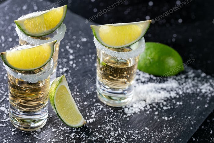Tequila with lime and salt on a black background