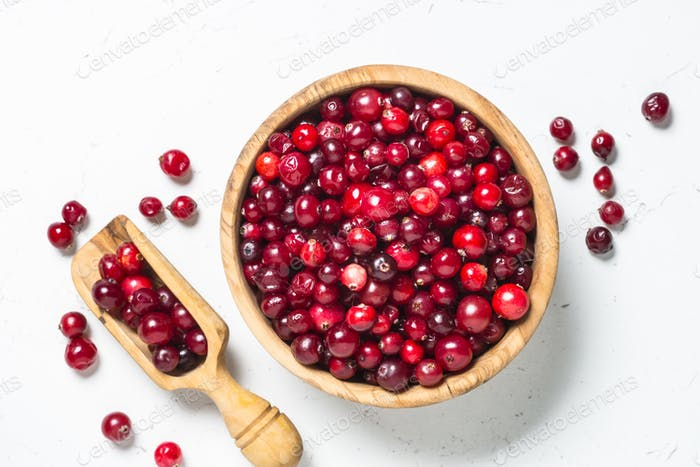 Cranberry in wooden bowl on white background