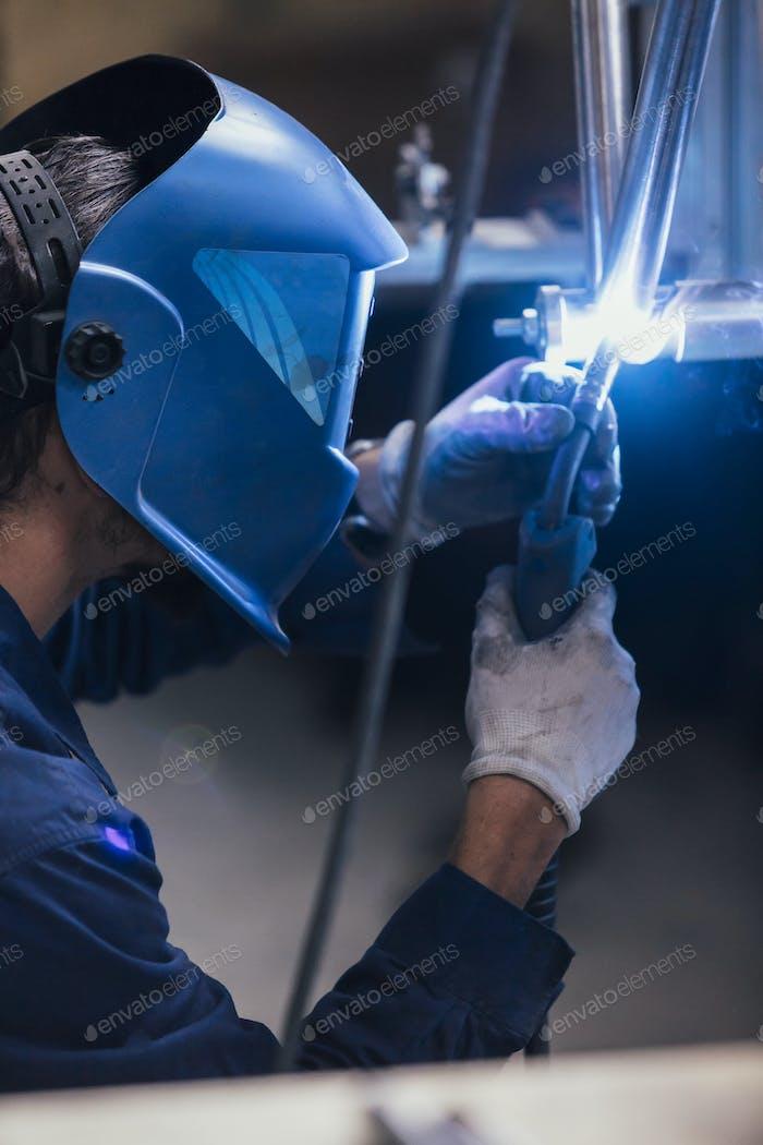 Worker welding metal detail