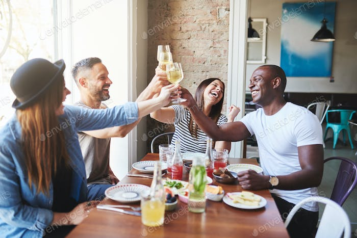 Happy adults toasting with drinks in restaurant