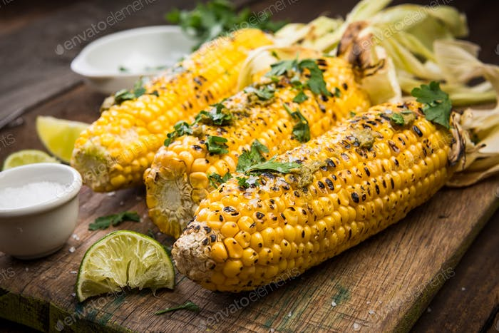 Grilled COrn on Cob with HErbs and Salt. Wooden Rustic Backgroun