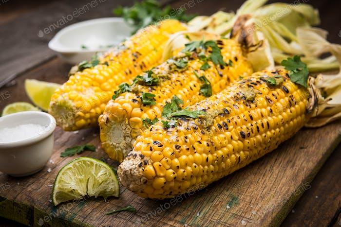 Gegrillter Mais auf Cob mit Kräutern und Salz. Rustikale Backgroun aus Holz