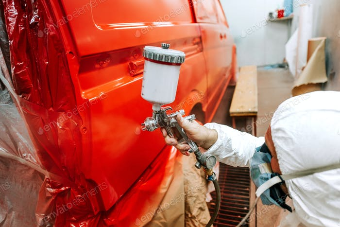 Close-up of man with spray gun with red paint painting a car in special booth