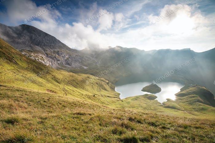 bright sunlight over alpine lake in fall